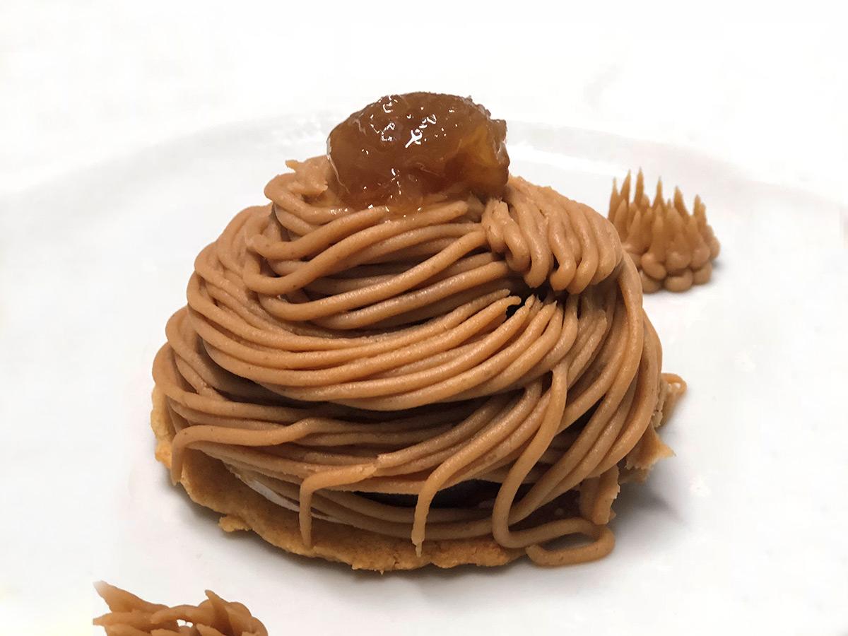 Mont Blanc cupola di cioccolato fondente ricoperta di crema di marroni e cacao con cuore cremoso al cioccolato bianco e biscotto alle mandorle